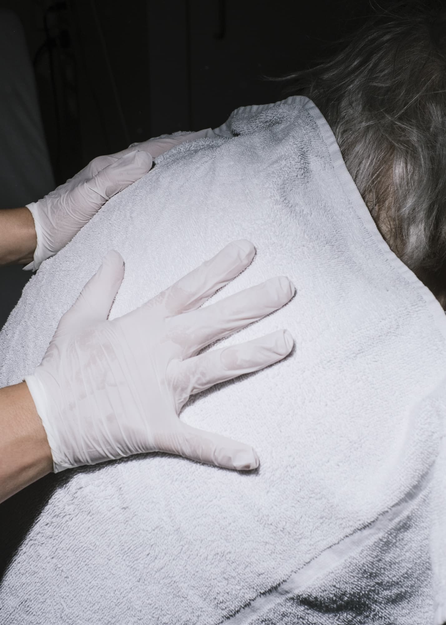 Nicht muede werden —  Hand detail of a nurse wiping sweat off a patient's back with a towel