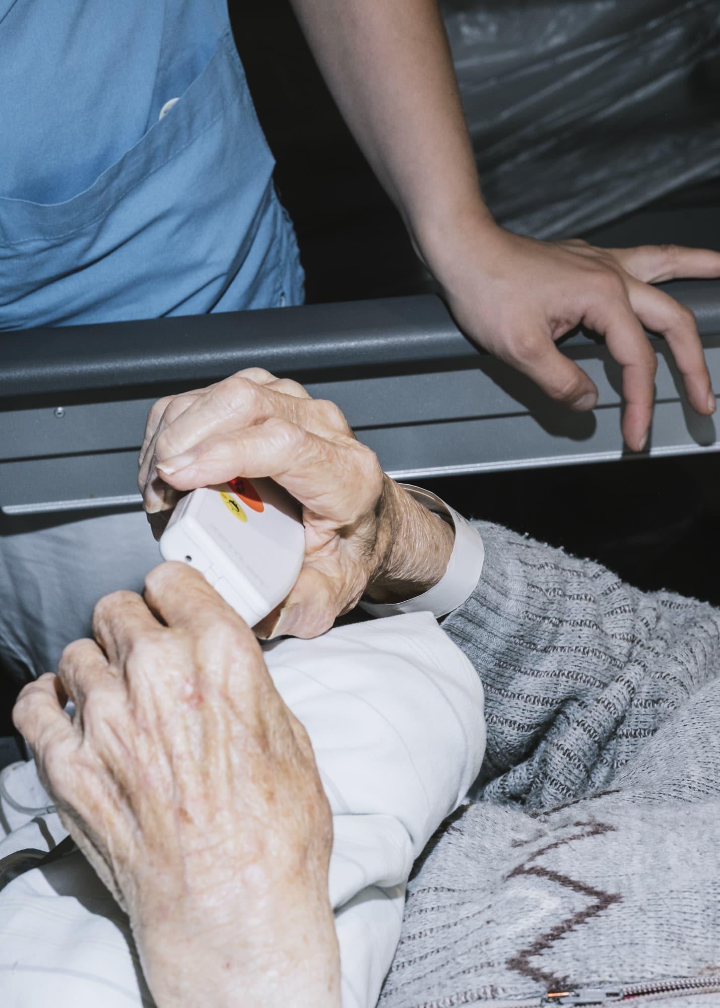 Nicht muede werden — Hand detail of a nurse reassuring a patient in bed