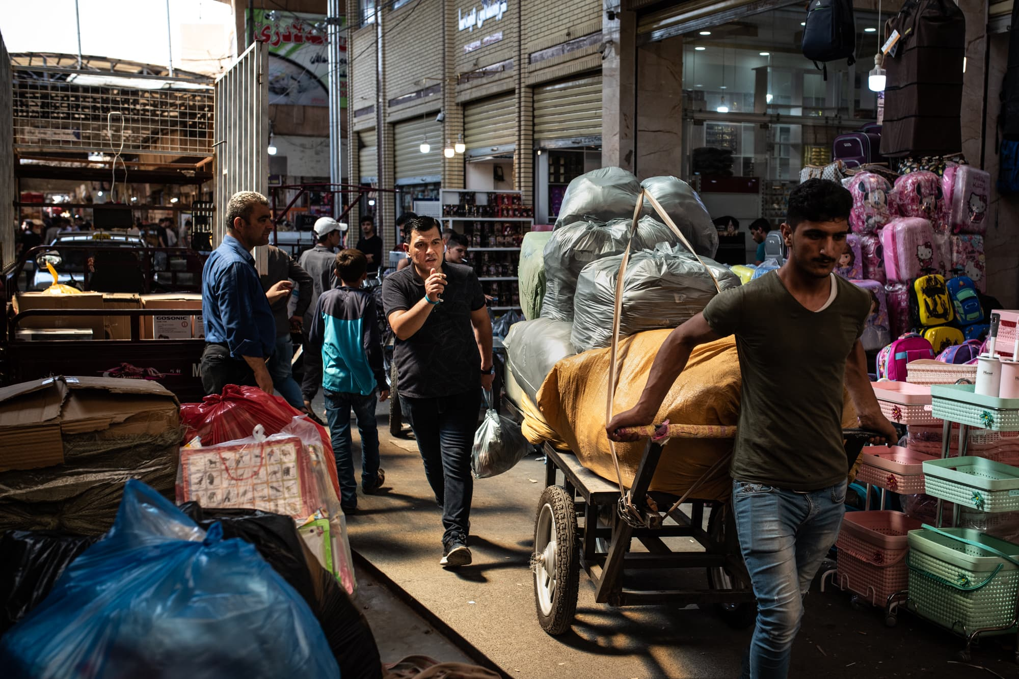 Abdullah Kurdi accompanies his newly bought school uniforms whilst they are being carried to his car through the busy market in Erbil, Iraq, on the 01.09.2019.