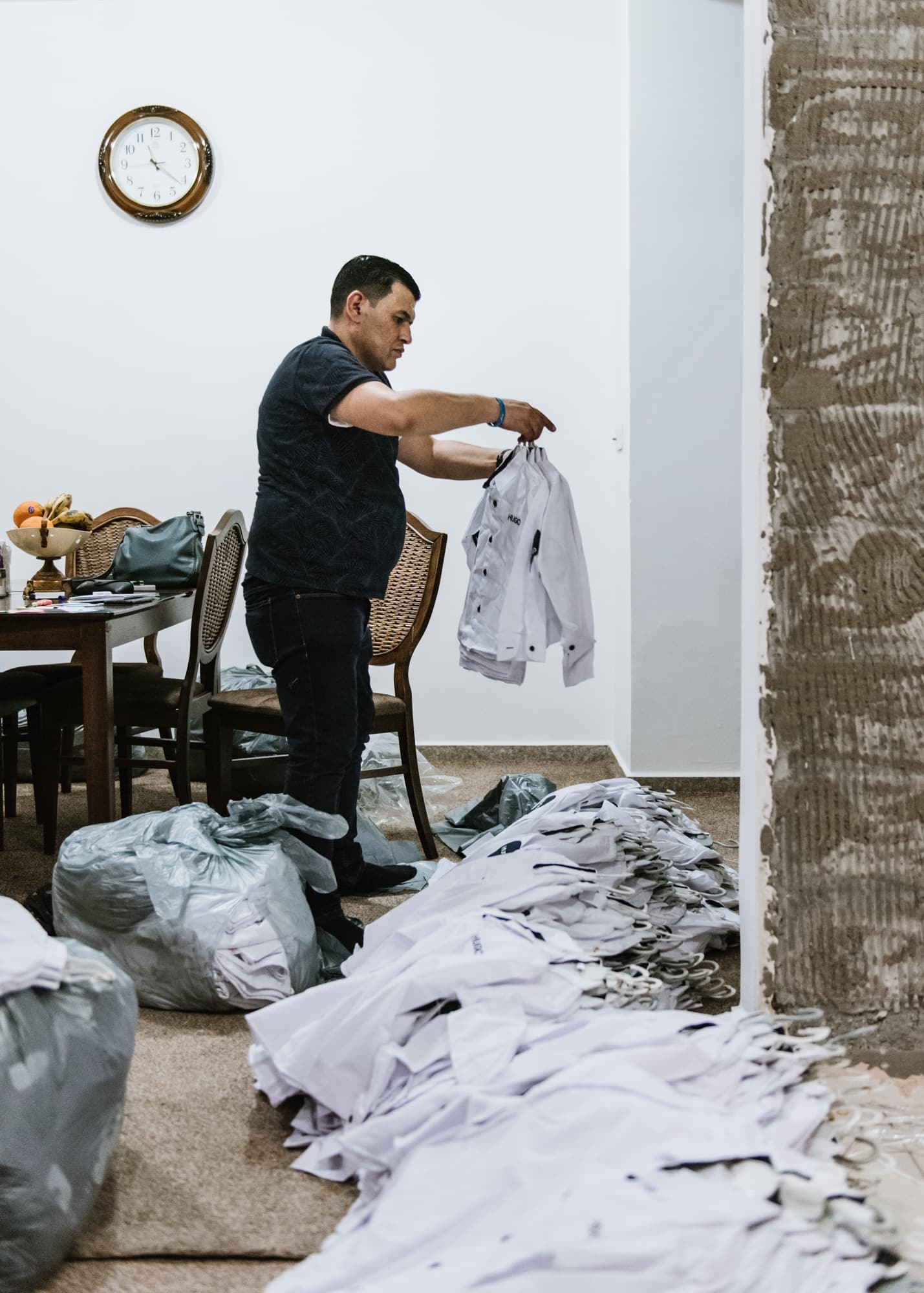On September 1st, 2019, Abdullah Kurdi sorts out school uniforms he plans to give away to refugee children the next day.