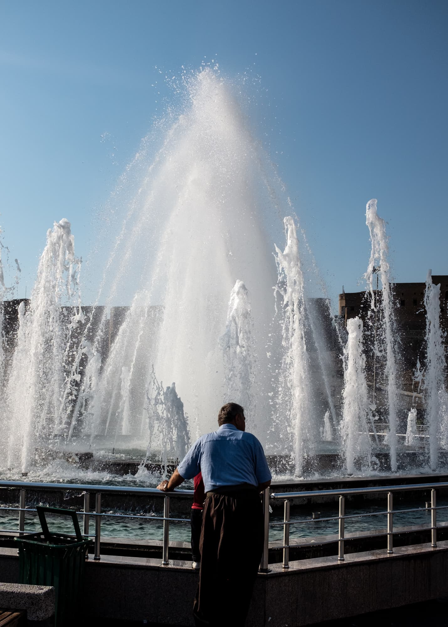 A man watches the water at a fountain with a boy in Erbil, Iraq, on Sept 3rd, 2019.