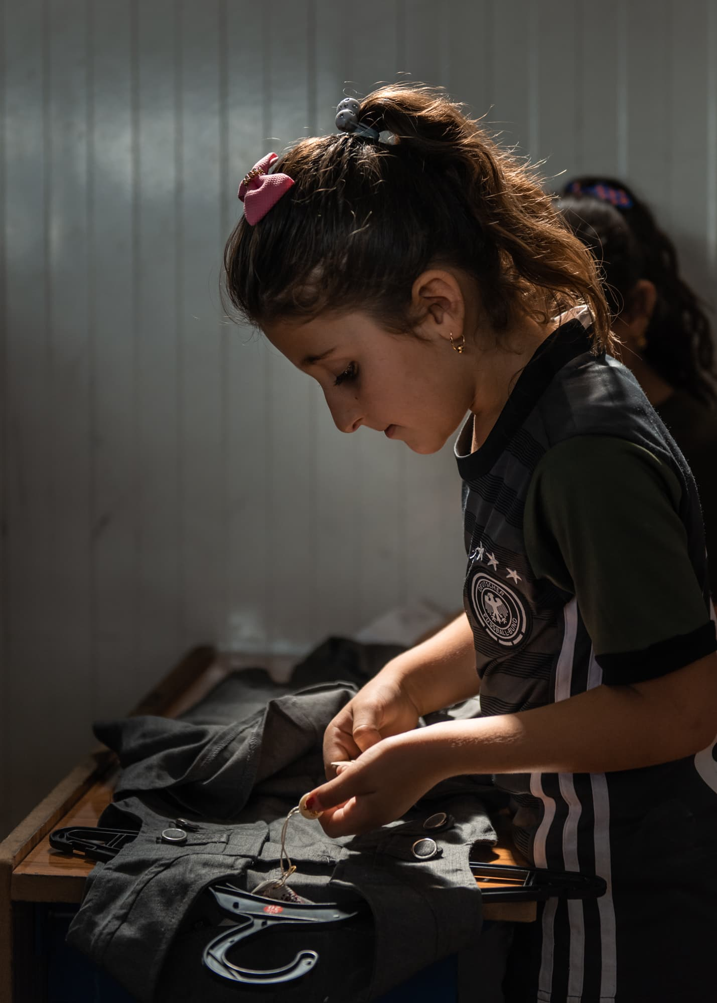 A young girl checks her new school uniform she got from Abdullah and Tima Kurdi at school at Gawilan refugee camp, Iraq, Sept 2nd, 2019.